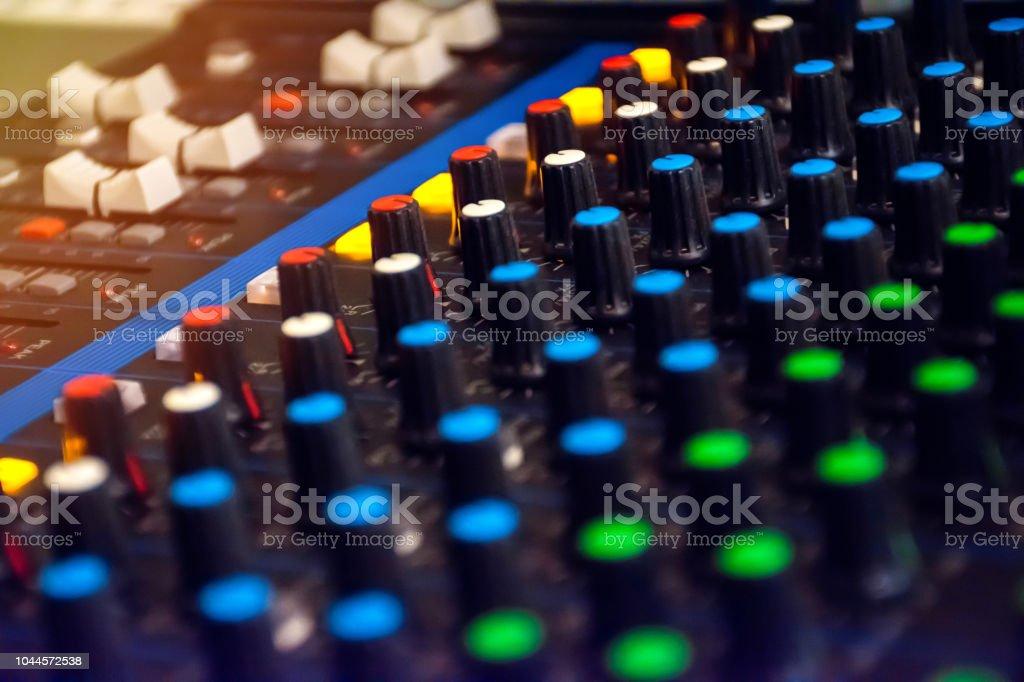 Sound mixer control panel on dark light background in audio control room. stock photo