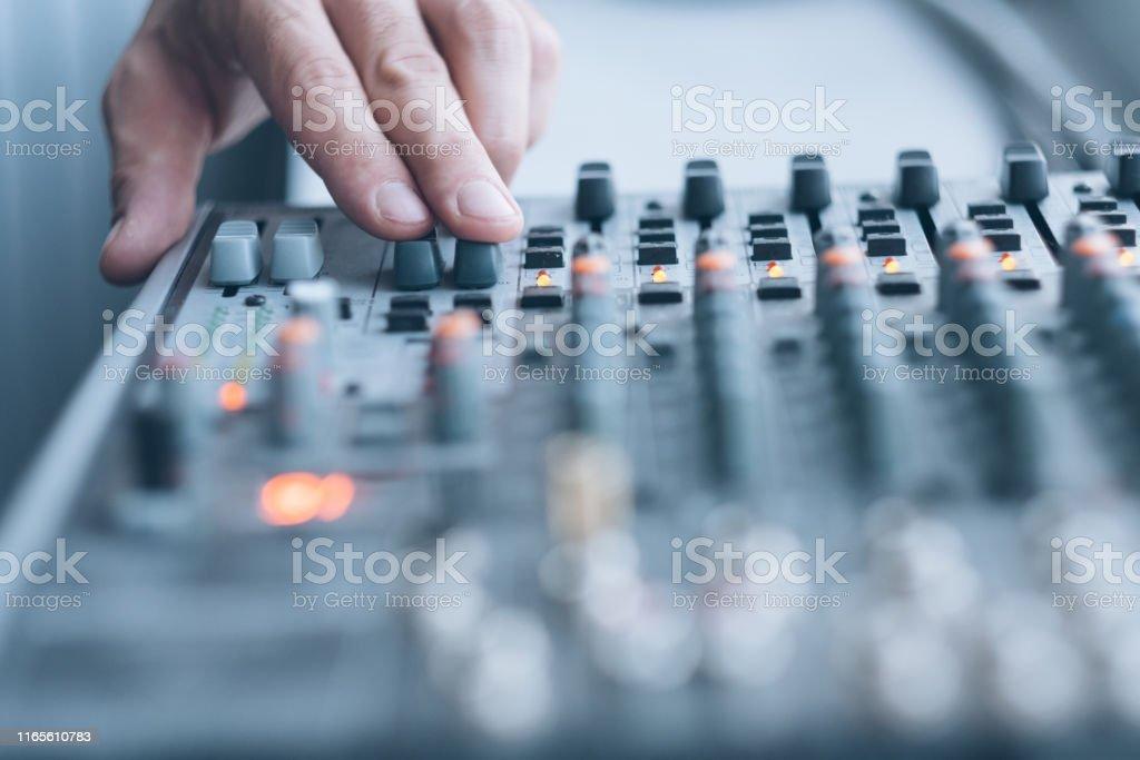 Sound recording studio. Closeup of man hand using professional audio...