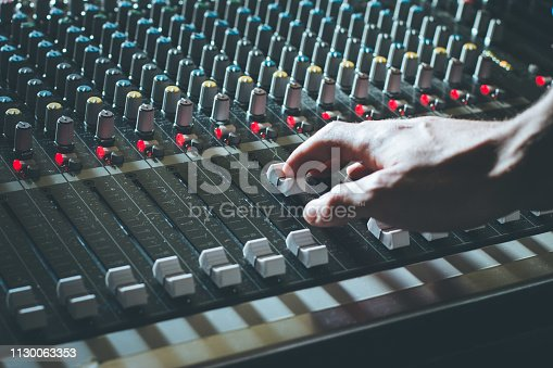 Professional music production in a sound recording studio, sound engineer is operating the mixing desk