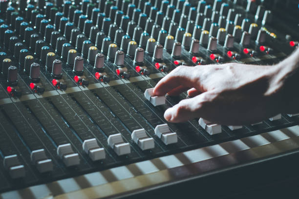 Sound recording studio mixer desk: professional music production Professional music production in a sound recording studio, sound engineer is operating the mixing desk sound mixer stock pictures, royalty-free photos & images