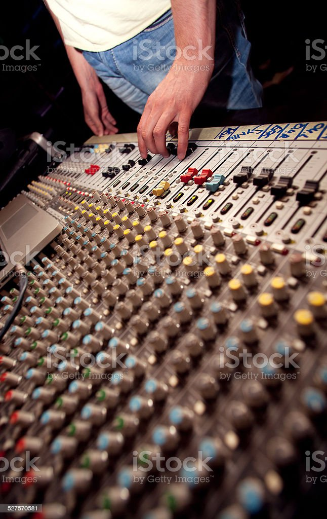 Soundman with mixing console in studio