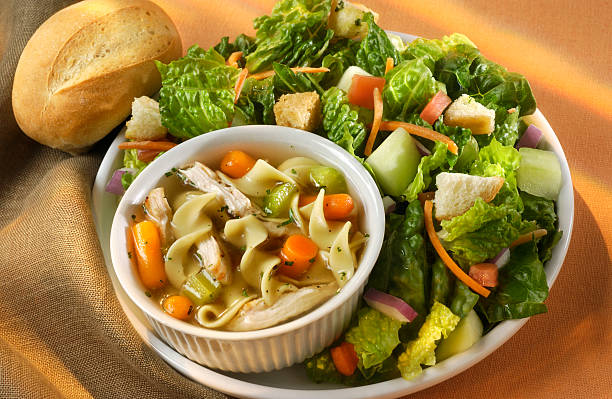 Soup and Salad Cup of chunky chicken noodle soup and fresh green salad.  Healthy Lunch or dinner.Shot with a Nikon. burwellphotography stock pictures, royalty-free photos & images