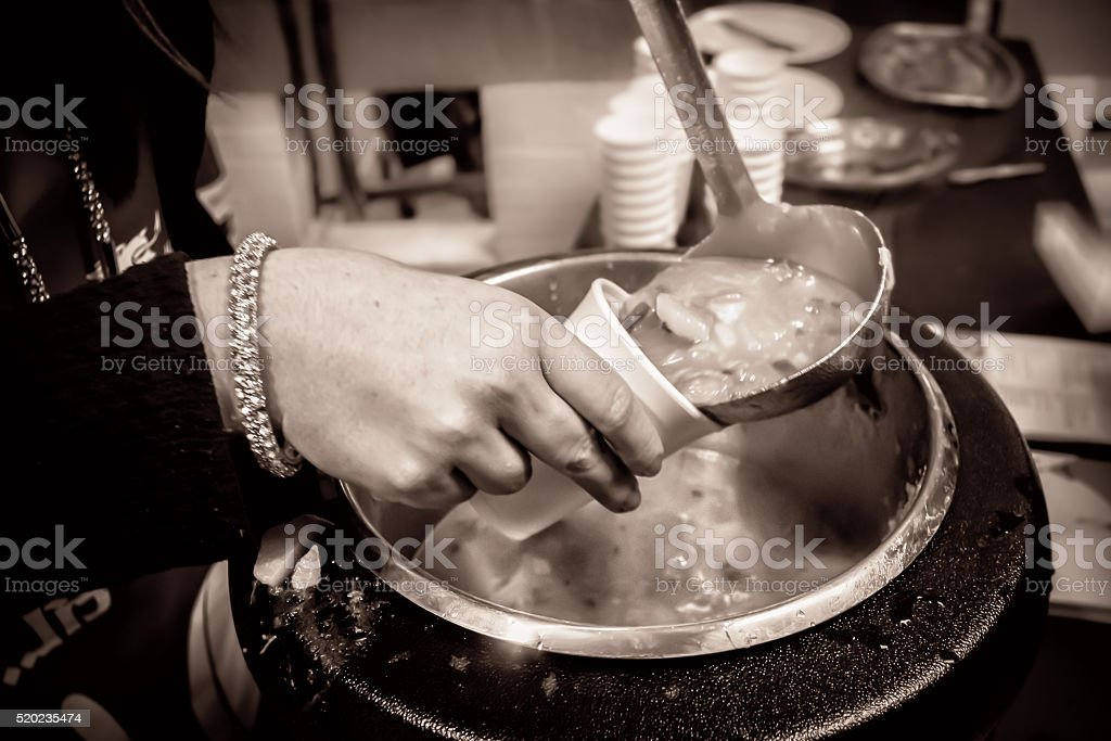 Soup being poured into a cup (monochrome) stock photo