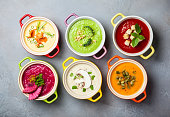 Variety of colorful vegetables cream soups in small pots. Top view. Concept of healthy eating or vegetarian food.