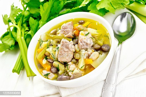 Eintopf soup of pork, celery, beans, carrots and potatoes with leek in a white bowl on a napkin on light wooden board background