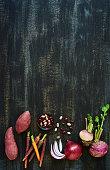 soup vegetables ingredients on dark rustic distressed background, sweet potato, heirloom carrots, kidney beans, onion, turnip