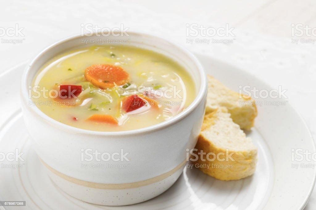 soupe aux légumes sains comme carotte, poivron rouge et le poireau dans un bol en céramique brillant avec pain sur une plaque, tableau blanc, gros plan photo libre de droits