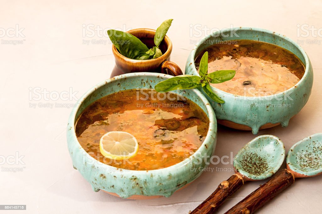 Soup with meat, smoked meat, sausages, pickled cucumbers, tomatoes, olives, herbs, lemon in blue bowl on gray concrete background, homemade food. Traditional Russian and Ukrainian soup solyanka. stock photo