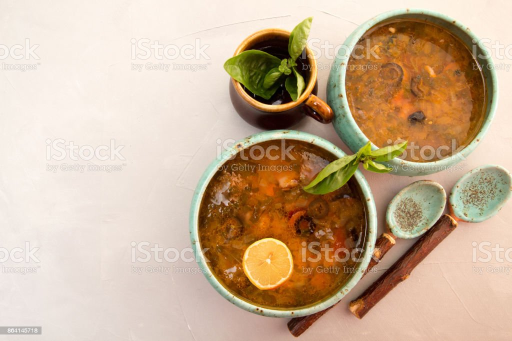 Soup with meat, smoked meat, sausages, pickled cucumbers, tomatoes, olives, herbs, lemon in blue bowl on gray concrete background, homemade food. Traditional Russian and Ukrainian soup solyanka. royalty-free stock photo