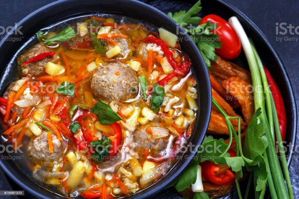 Soupe aux boulettes de viande dans un plat noir, légumes émincés - oignon, persil, poivron, tomate, sur un fond noir photo libre de droits