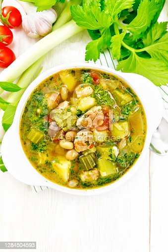 Soup with pisto sauce, lard, tomatoes, zucchini, beans, celery and leeks in a bowl on a towel on wooden board background from above