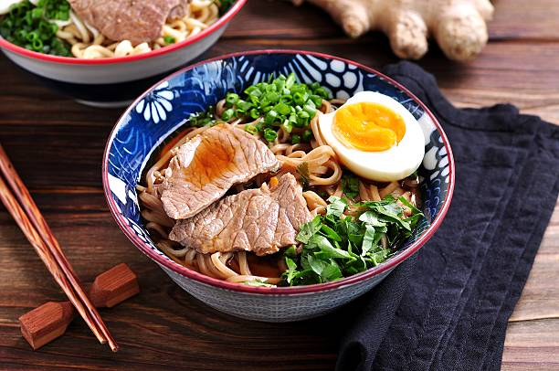 soup with soba and ramen noodles, beef, ginger, green onions - japanisches essen stock-fotos und bilder