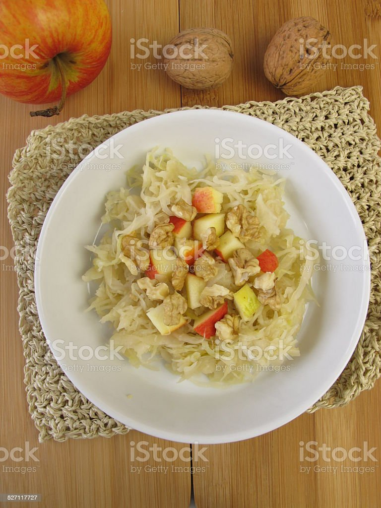 Sour cabbage salad with apples and walnuts stock photo