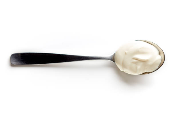 Sour cream in a spoon isolated on white, from above stock photo