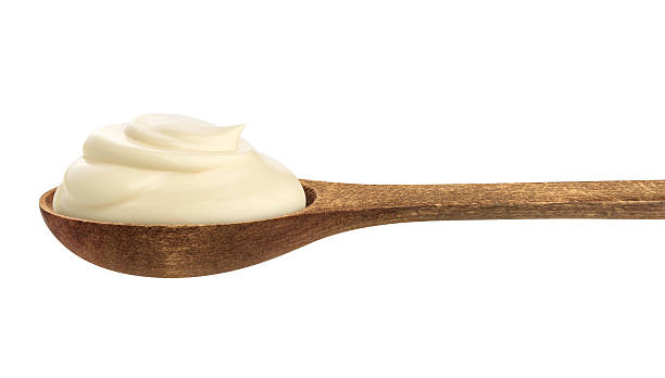 Sour cream in wooden spoon isolated on white background stock photo