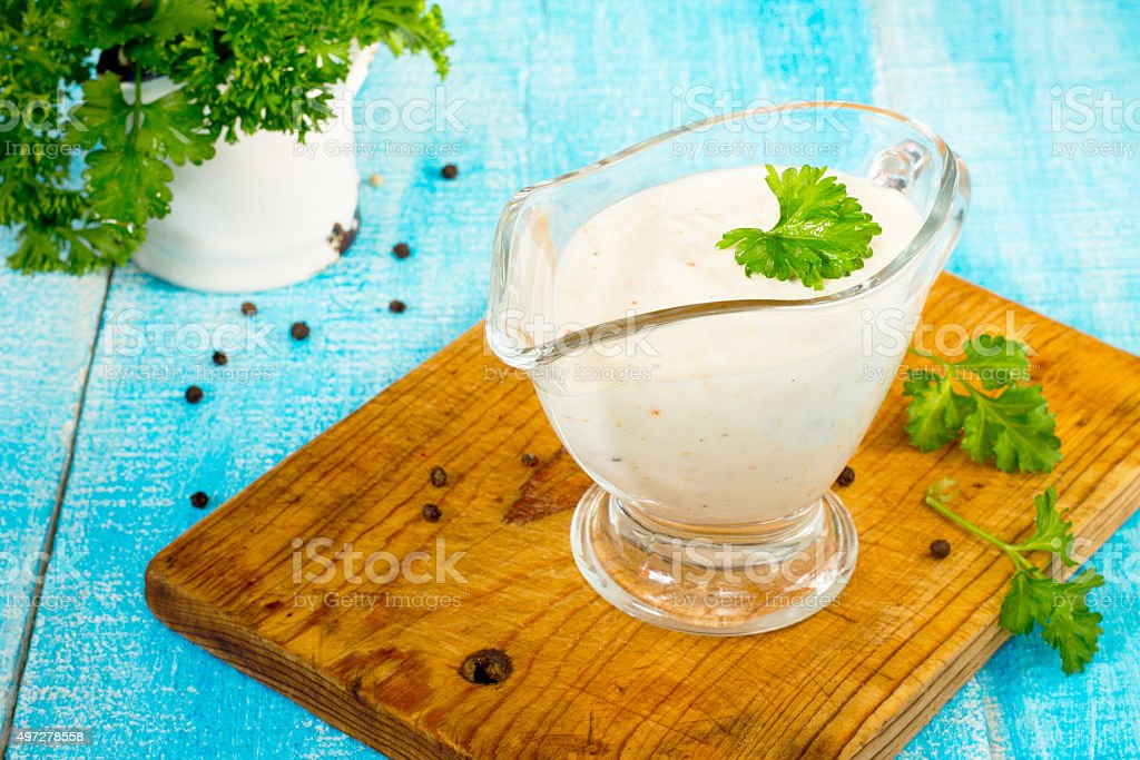 Sour cream sauce with spices in a glass gravy boat stock photo