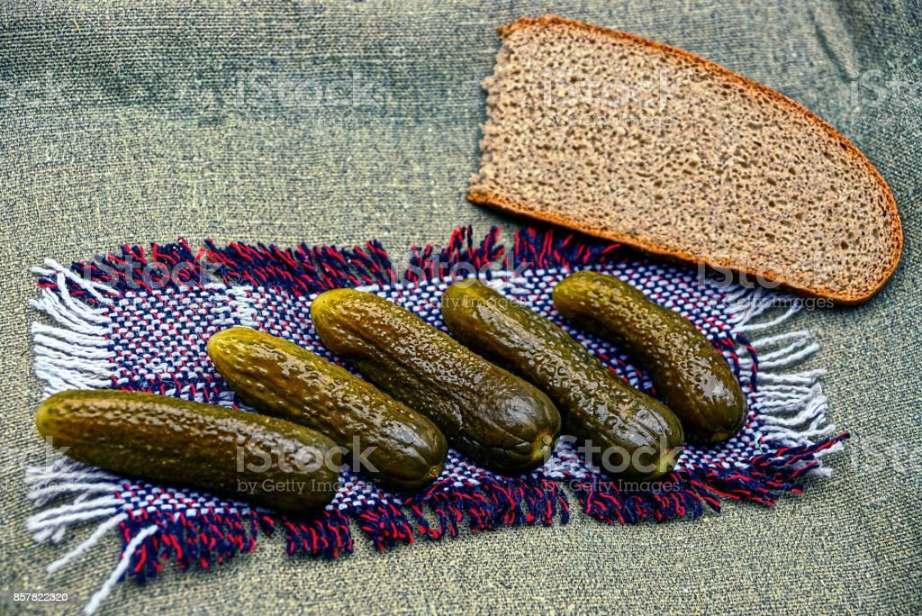 Sour cucumbers and a piece of bread on a wool rug stock photo