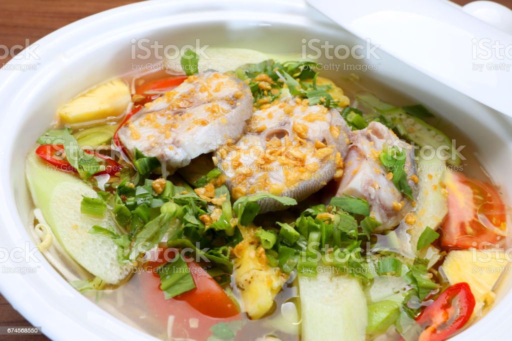 Sour soup in Vietnamese style with grouper fish in white bowl stock photo