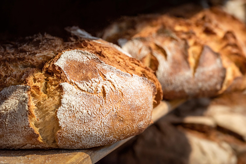 Sourdough bread close-up. Freshly baked round bread with a golden crust on bakery shelves. German baker shop context with rustic bread assortment.