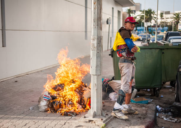sousse, tunisia-09/17/2019: city street, sousse. a local resident in dirty clothes dancing next to the fire, near the garbage. drawing attention to himself, he begins to pose. - dumpster fire zdjęcia i obrazy z banku zdjęć
