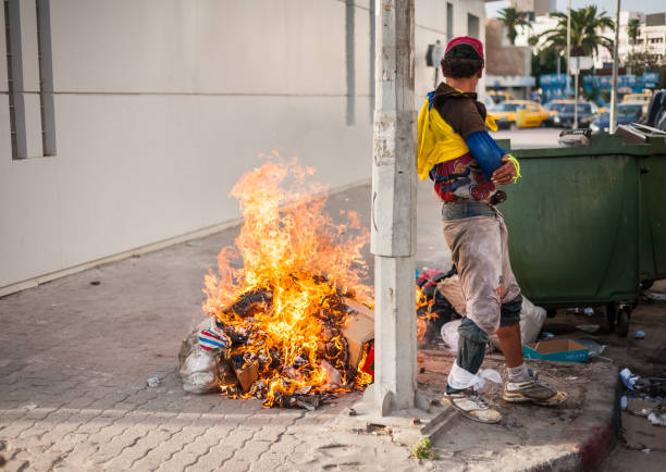 Sousse, Tunisia-09/17/2019: City street, Sousse. A local resident in dirty clothes dancing next to the fire, near the garbage. Drawing attention to himself, he begins to pose. Sousse, Tunisia-09/17/2019: City street, Sousse. A local resident in dirty clothes dancing next to the fire, near the garbage. Drawing attention to himself, he begins to pose. dumpster fire stock pictures, royalty-free photos & images
