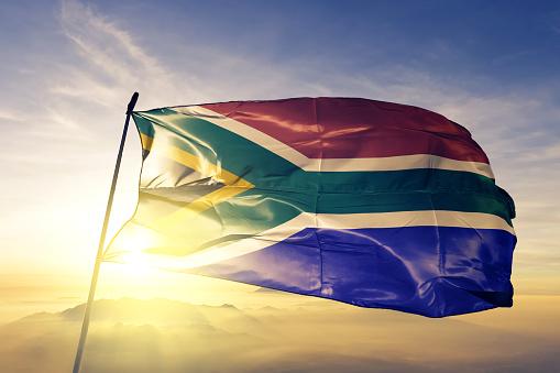 South Africa African flag on flagpole textile cloth fabric waving on the top sunrise mist fog
