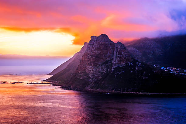 South Africa - dramatic skies at Hout Bay; Blue Hour Sunset at Hout Bay in the Western Cape Province of South Africa.  The rays of the setting sun hit the mountain side and bring out the dramatic colours of the cliffs. The sky ablaze with the colours of the setting sun. Some houses and buildings can be seen to the right of the photo. The peak to the centre of the photo is locally known as The Sentinel. Photo shot in the horizontal format, in the Blue Hour; copy space. No people. hout stock pictures, royalty-free photos & images