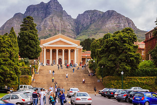 South Africa - University of Cape Town Cape Town, South Africa - April 17, 2007: The main building in the University of Cape Town in South Africa. Several cars are parked in front of the steps to the building. Many students can be seen walking away or to the building; some just sit on the steps relaxing or chatting with friends. Photo shot in the afternoon sunlight; horizontal format.  chandra dhas, stock pictures, royalty-free photos & images