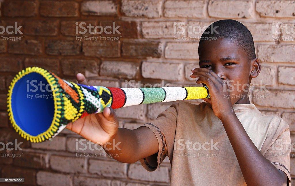 South African boy blowing Vuvuzela stock photo