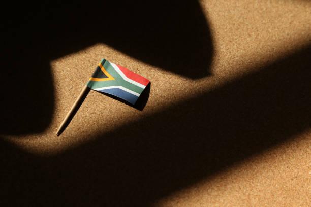 一面被陰影包圍的南非國旗。政府法規概念形象。 - black power 個照片及圖片檔