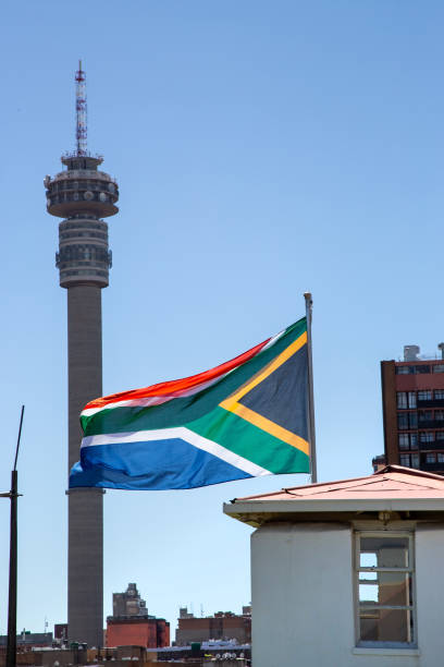 South African flag with city buildings in background stock photo