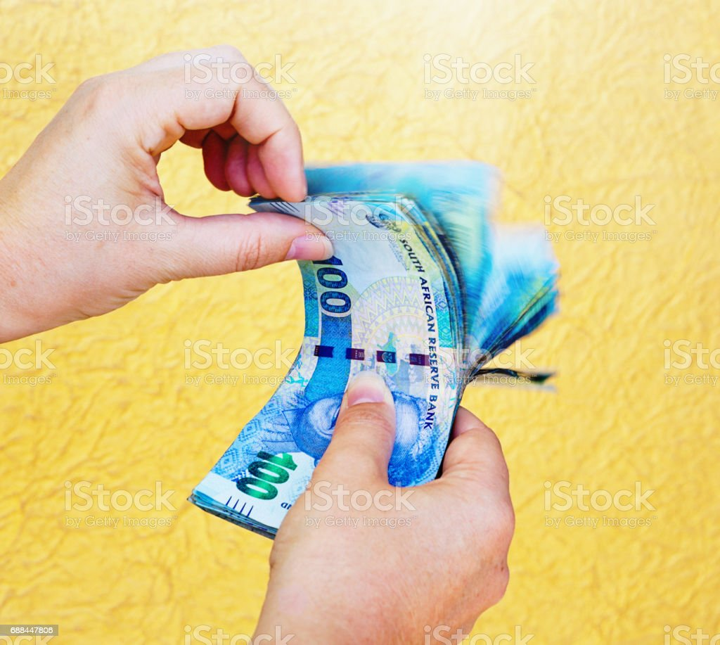 South African money: hands riffle through banknotes, counting stock photo