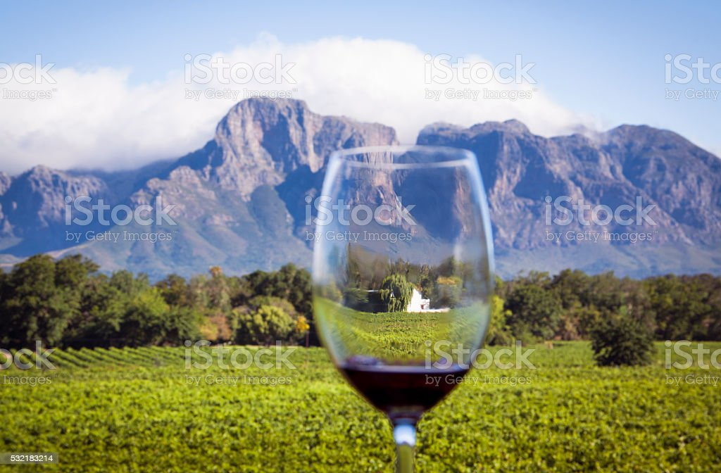 South African Wine Country Classic landscape of vineyard, estate house and mountains in the Western Cape, South Africa, with wine glass foreground.   Agriculture Stock Photo