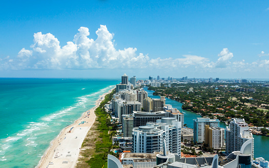 Looking down South Beach in Miami. Full view of the beach on the left and the city on the right. Beautiful blue sky on a clear day.