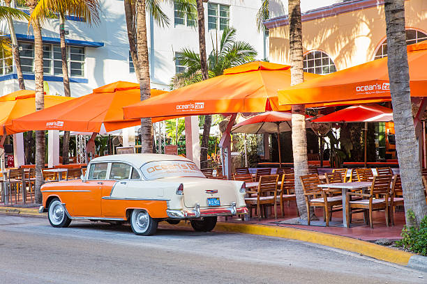 South Beach Miami Florida Miami Beach, Florida, USA - April 24, 2016: View along the famous vacation and tourist location on Ocean Drive in the Art Deco district of South Beach, Miami on a sunny day with cars,  palm trees and people visible.  groyne stock pictures, royalty-free photos & images