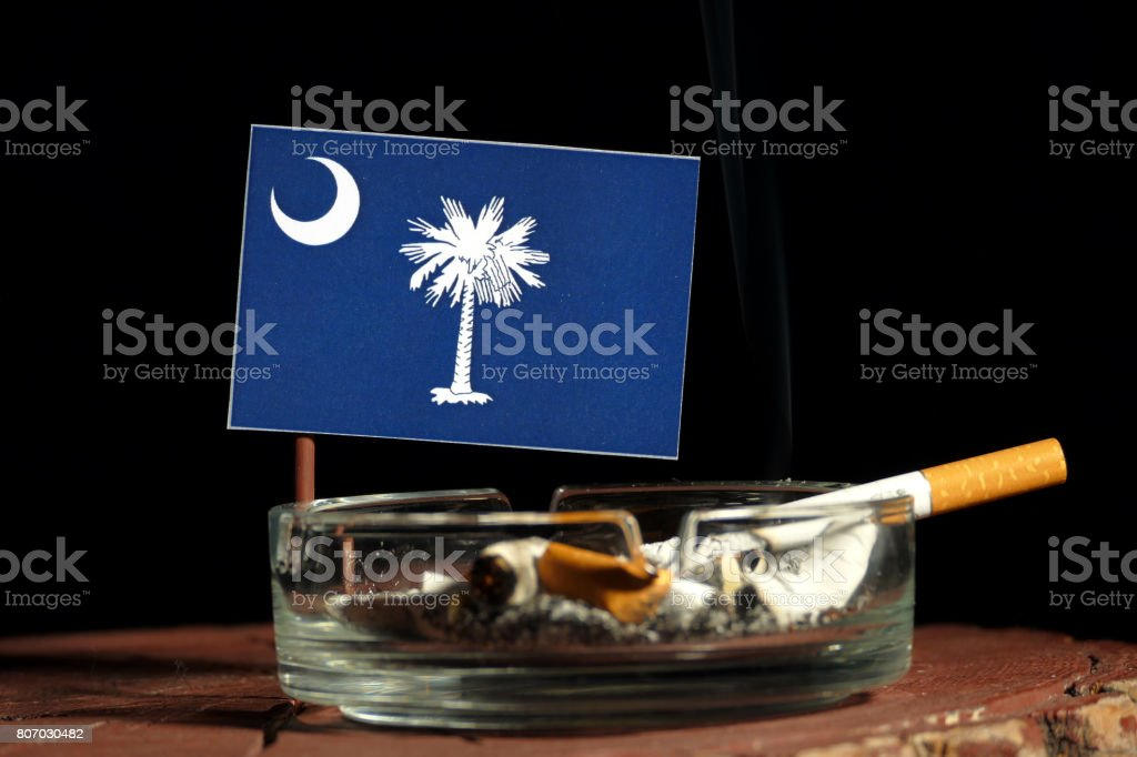South Carolina flag with burning cigarette in ashtray isolated on black background stock photo