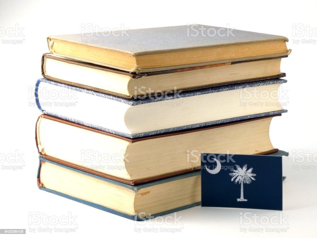 South Carolina flag with pile of books isolated on white background stock photo