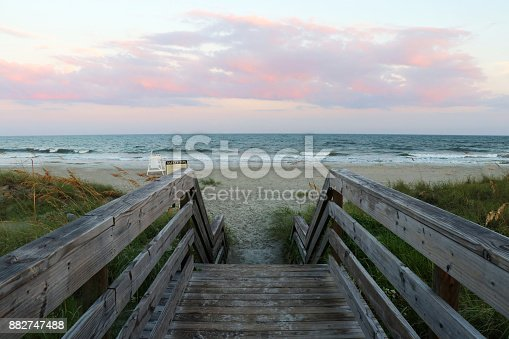 Wooden boardwalk and stairs to the ocean beach over sand dunes in Huntington Beach State Park, Myrtle Beach area, South Carolina, USA. After sunset seascape.