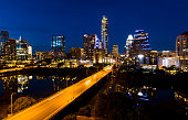 Aerial drone motion cars driving across bridge over town lake with skyline cityscape at night reflections off night Colorado river city at night - South congress bridge time lapse nightscape - Austin , Texas