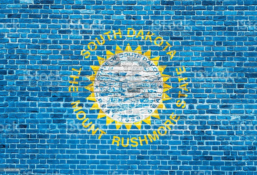 South Dakota US flag painted on old vintage brick wall stock photo