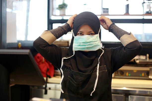 South East Asia: At The Airport A Muslim female adult is positioning and tying surgical mask strap at airport cafe in Malaysia. kuala lumpur airport stock pictures, royalty-free photos & images