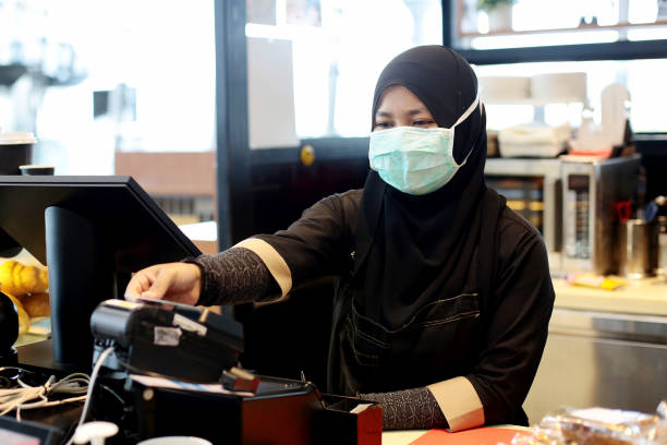 South East Asia: At The Airport A Muslim female adult is holding credit card for processing payment at airport cafe cashier counter in Malaysia. kuala lumpur airport stock pictures, royalty-free photos & images