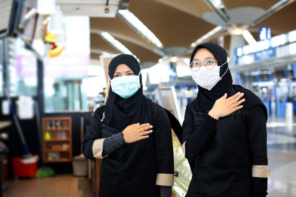 South East Asia: At The Airport Two Muslim female adults are placed their right hand on left chest as an alternative to handshakes at airport cafe in Malaysia. kuala lumpur airport stock pictures, royalty-free photos & images