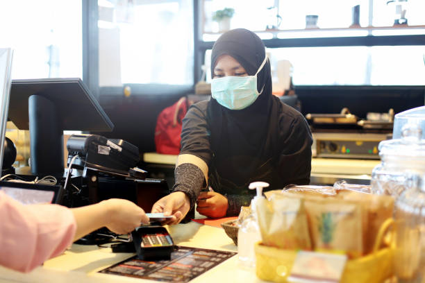 South East Asia: At The Airport A Muslim female adult is holding credit card for processing contactless payment at airport cafe cashier counter in Malaysia. kuala lumpur airport stock pictures, royalty-free photos & images