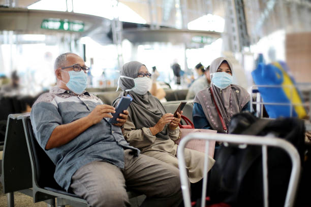 South East Asia: Muslim Family Travel A Muslim senior man and two senior women are  sitting patiently waiting for flight boarding at Malaysia airport. kuala lumpur airport stock pictures, royalty-free photos & images