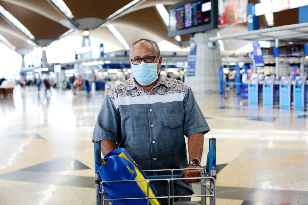 South East Asia: Muslim Family Travel A senior Muslim man is pushing trolley at Malaysia airport waiting for flight boarding. kuala lumpur airport stock pictures, royalty-free photos & images