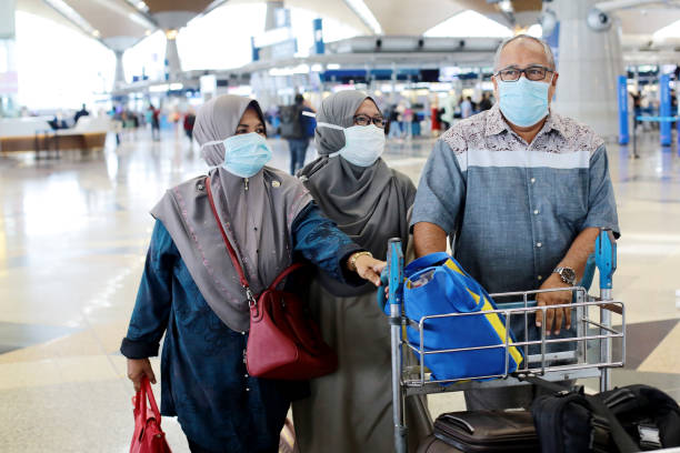 South East Asia: Muslim Family Travel A senior Muslim man and two senior women pushing trolley at Malaysia airport waiting for flight boarding. kuala lumpur airport stock pictures, royalty-free photos & images