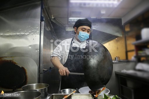 A Malaysian ethinicity male adult chef is preparing food from commercial kitchen in Kuala Lumpur, Malaysia.
