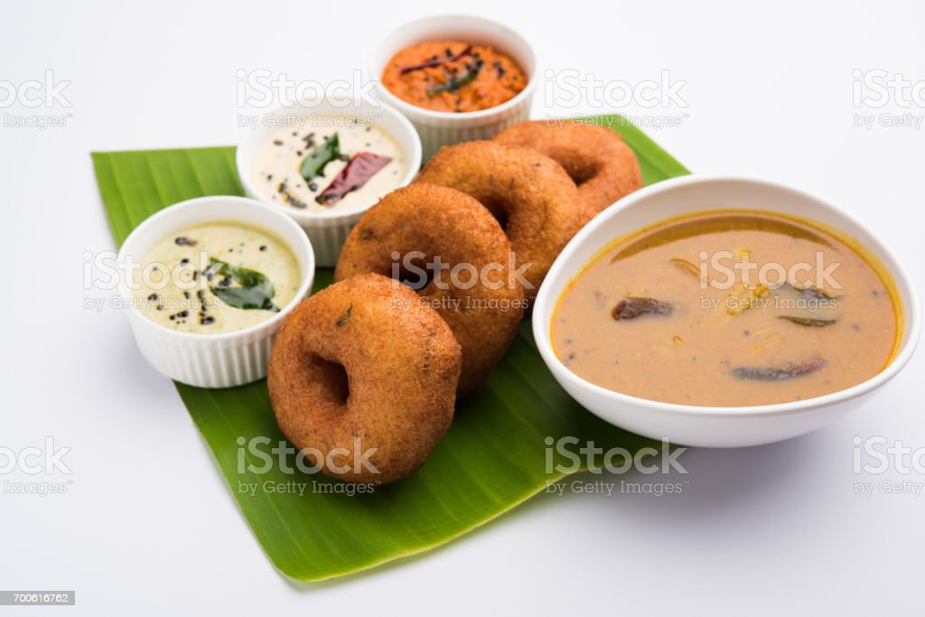 south indian food called vada sambar or sambar vada or wada, served with coconut, green and red chutney and south indian style hot coffee, selective focus stock photo