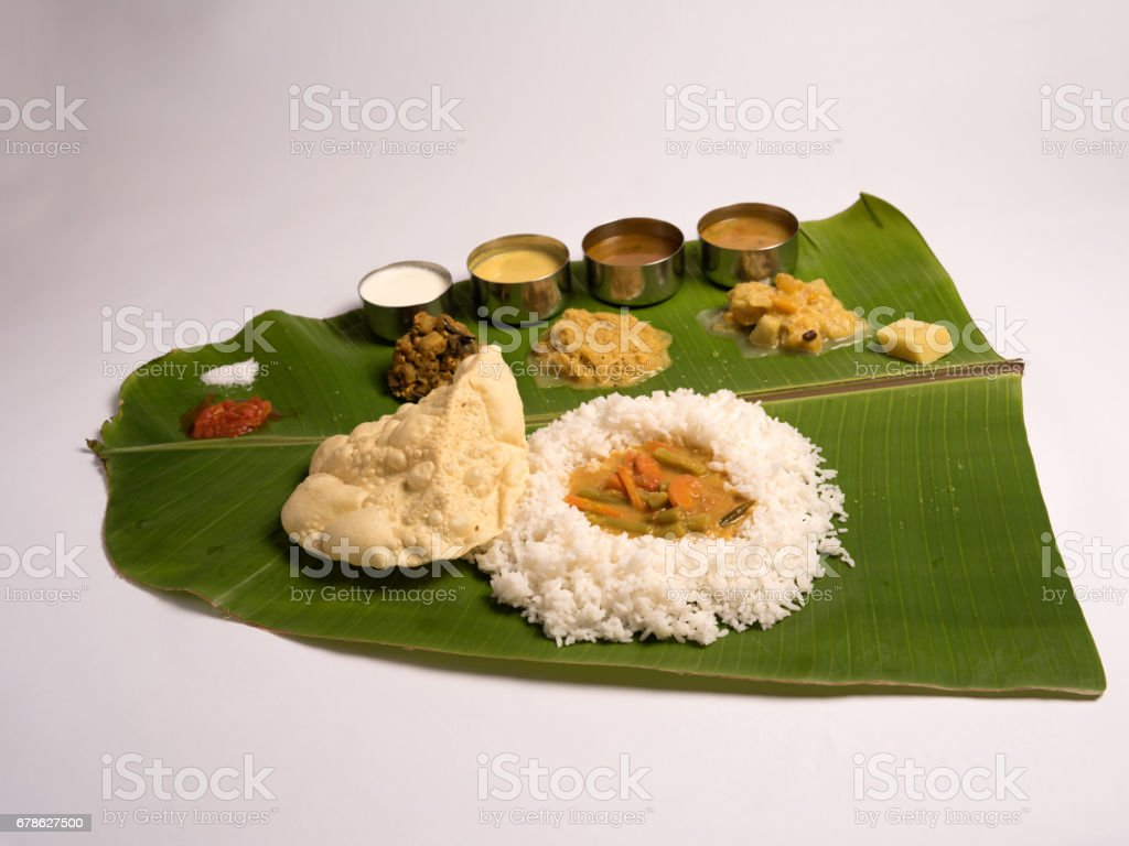 south indian meals served in a banana leaf on white background stock photo